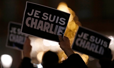 Persons hold placards saying Je Suis Charlie - I am Charlie